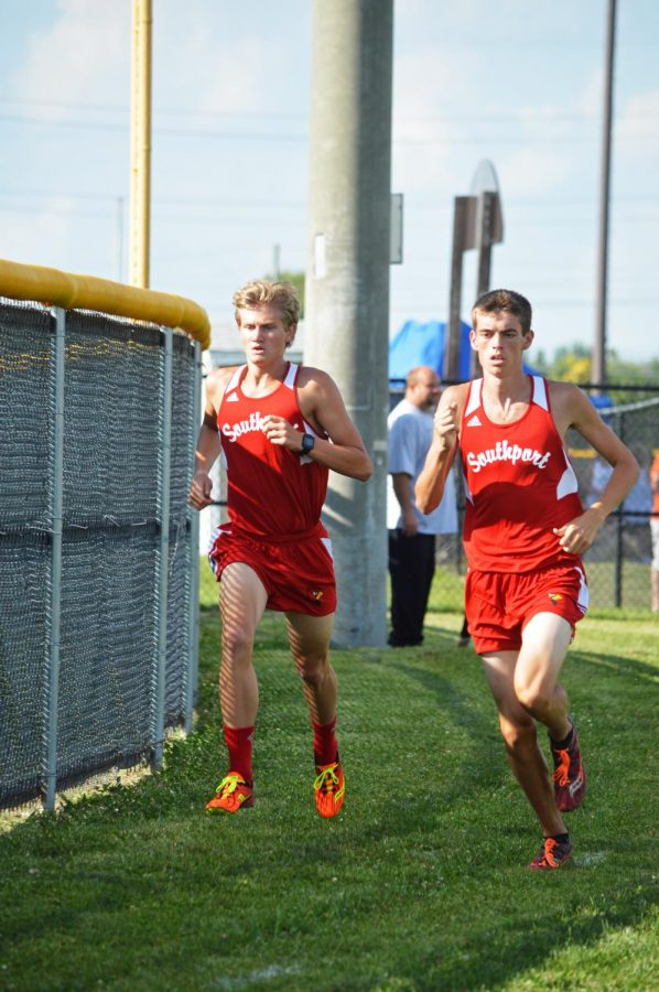 Michael Crook (right) runs alongside a teammate in a meet against Perry Meridian on Aug.15.