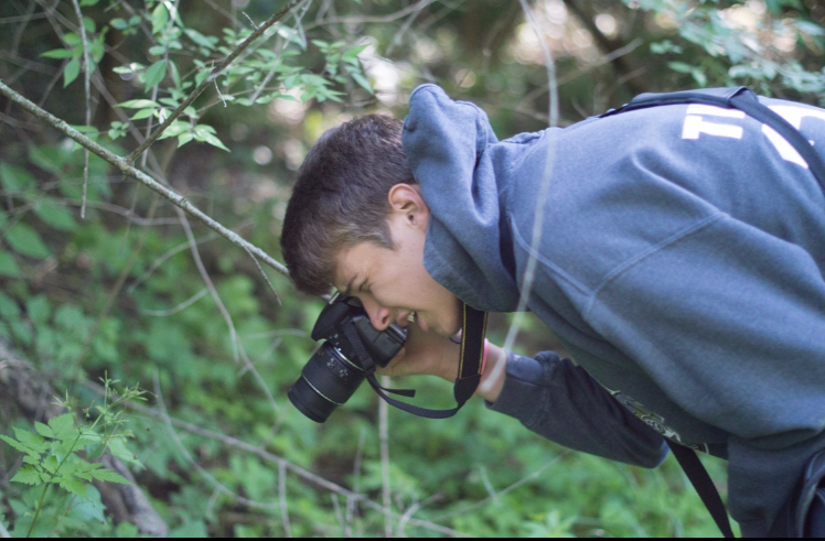 Junior Noah Thomas takes a photo of some plants in the woods behind his house.