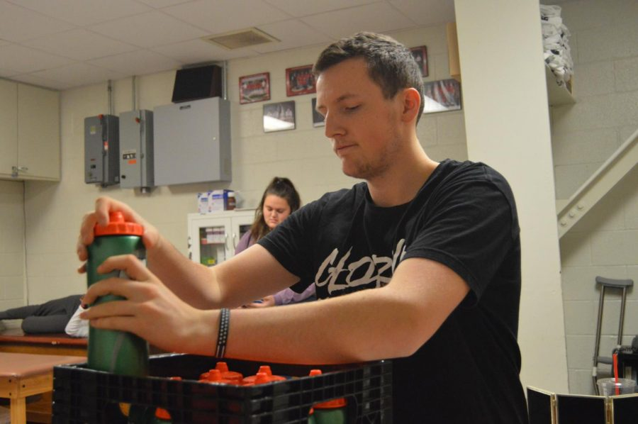Senior Austin Taylor fills up the water bottles for the boys basketball team before a practice on Dec. 7.