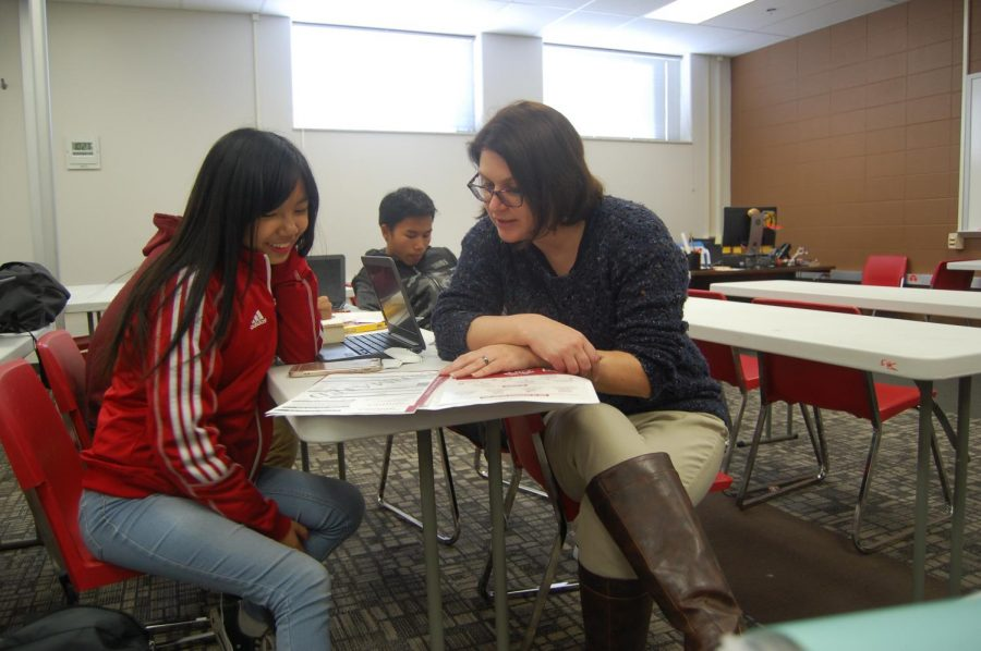 English+teacher+Amy+Peddie+helps+senior+Iang+Len+sort+through+her+FASFA+paperwork+during+ipass+on+Thursday%2C+Dec.+14.