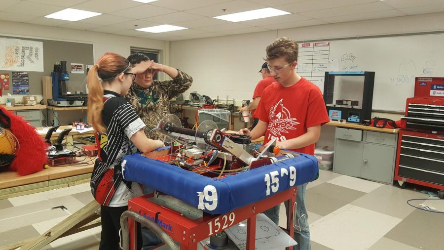 Junior Anthony Borho works on the robot along with other Cyber Cards members.