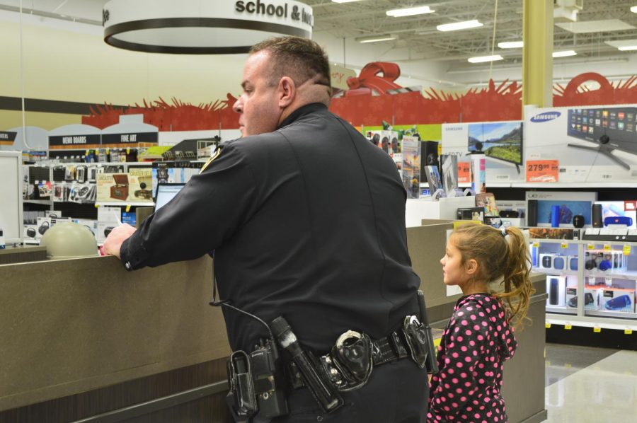 Doug Wood, a cop, and, Jacqueline,  a daughter from another family check out at the desk after shopping together.