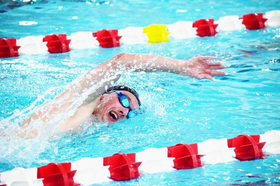 Senior Noah Fishel swims freestyle during a meet in this past season. Fishel is one of the team's best returning swimmers.