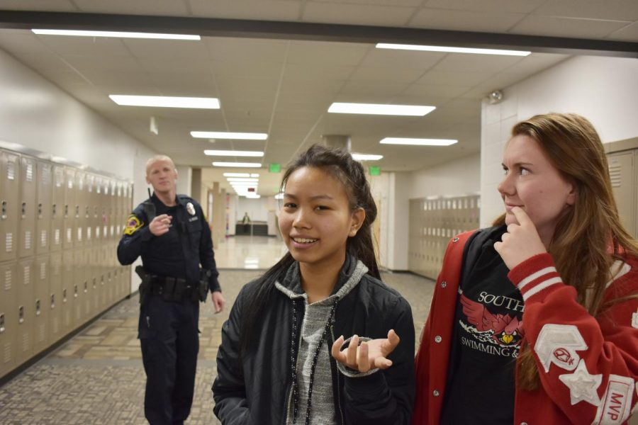 "Juniors Makayla Crawford (middle) and Regina Phalange (right) are confronted by Officer Harold McKinley (left) during a passing period. ""Tell me why this cop asked for my license and registration,"" Crawford said."