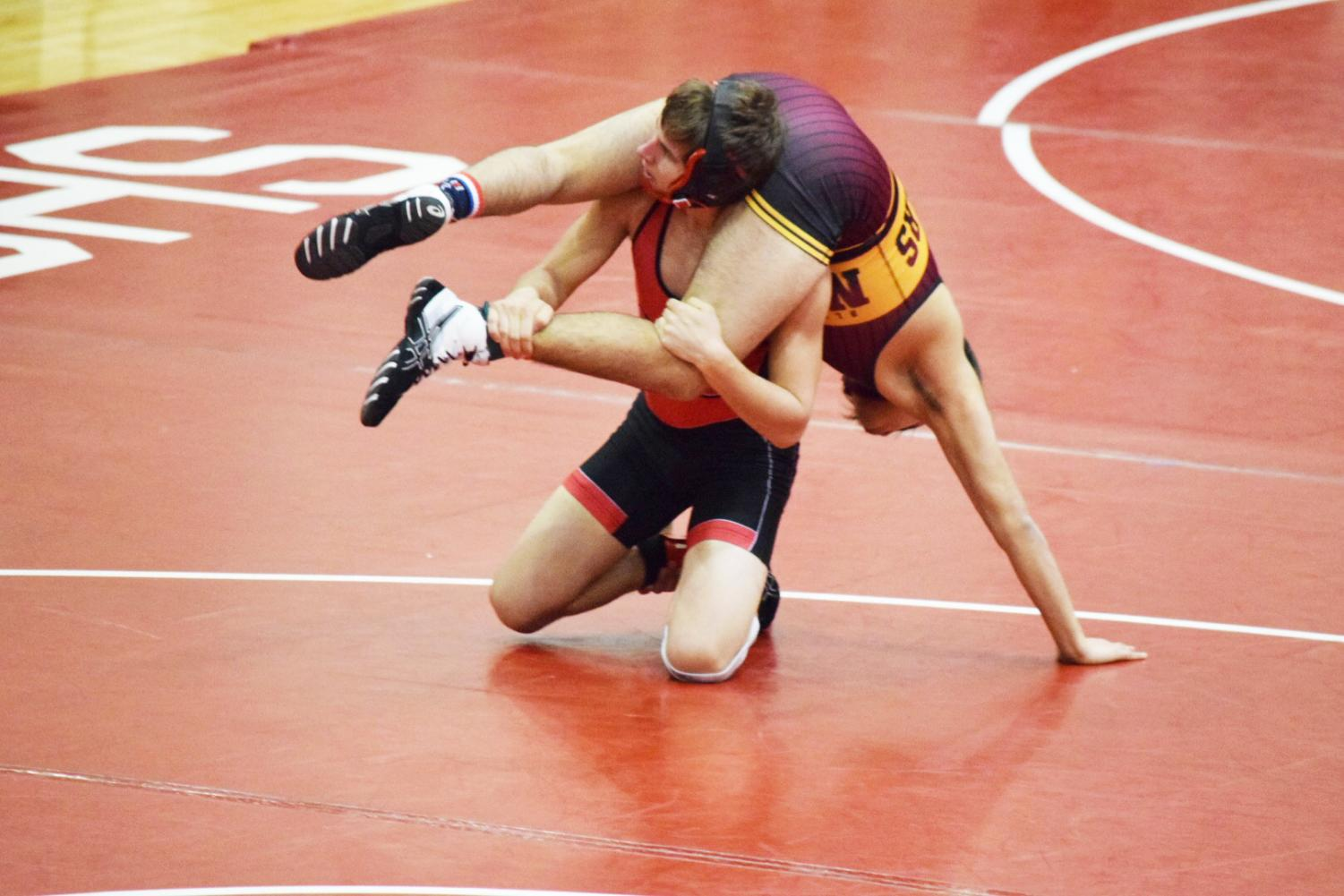 Junior Justin Tracy wrestles an opponent in the conference meet on Jan. 19.