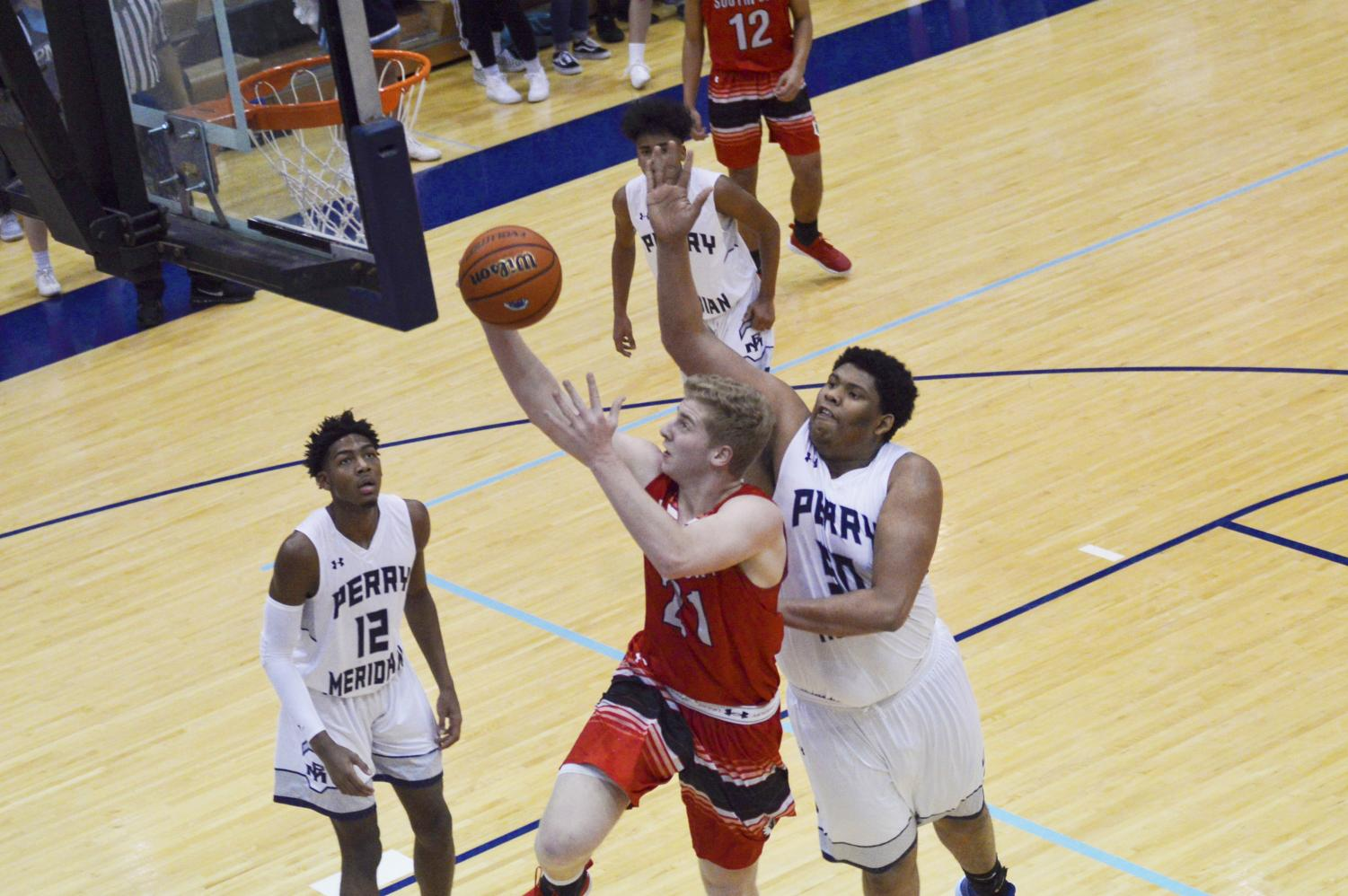 Junior Eddie Schott goes up for a layup during the Perry Meridian basketball game on Feb. 1 at PMHS. Schott led the Cards in scoring with 23 points in their 71-57 victory.