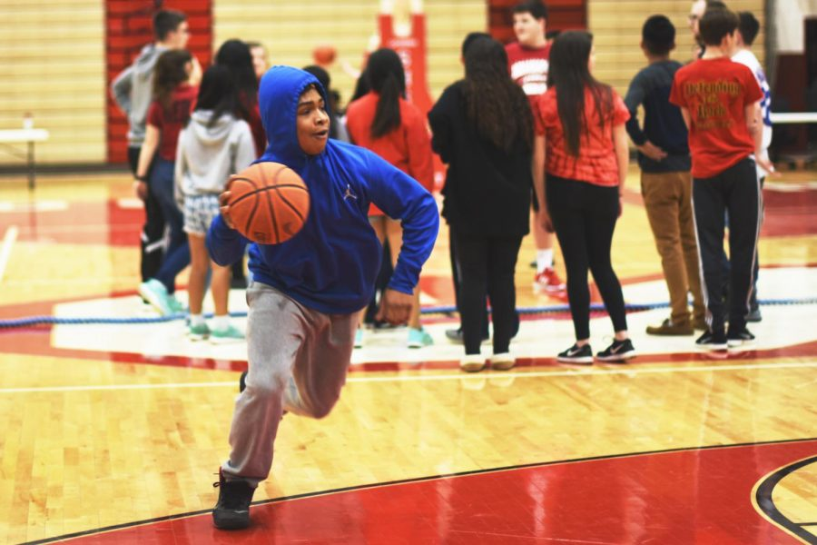 Freshman Gage Nelson dribbles the ball against his opponent from the junior class for the one-on-one class basketball competition during the Snowcoming Spectacular.