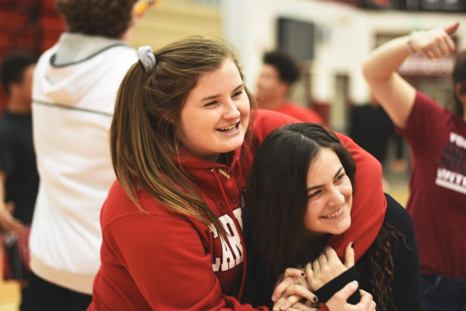 Senior Emily Chambers and sophomore Grace Campbell dance together to a song being played over the speakers during the snowcoming spectacular on Feb. 9.