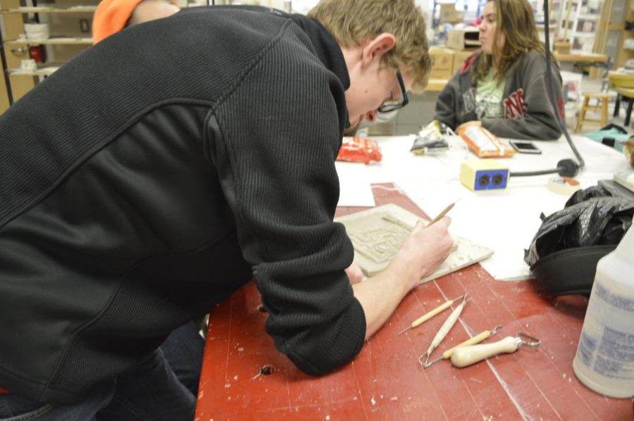 Senior Zyon Johnston works on his sculpture on March 8 during iPass.