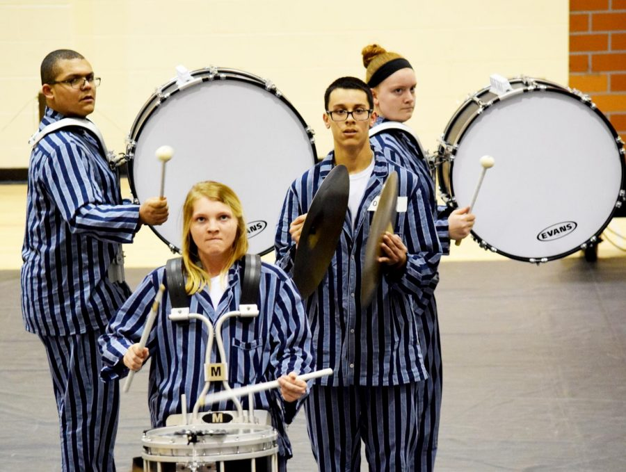 Freshman Theron Jackson, senior Alyson Riddle, sophomore Toby Brummett and freshman Lauren Query (L to R) march during the first movement of the performance.