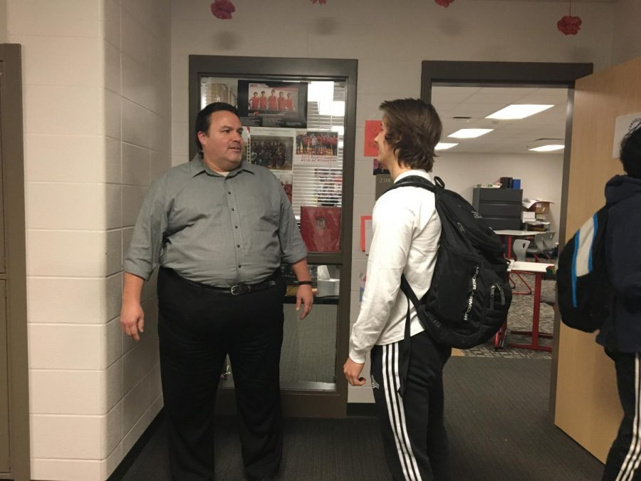 Geography teacher and men's volleyball coach Joseph Leonard interacts with students in the hallway on Tuesday, March 13 after school. Leonard has been teaching for 14 years.