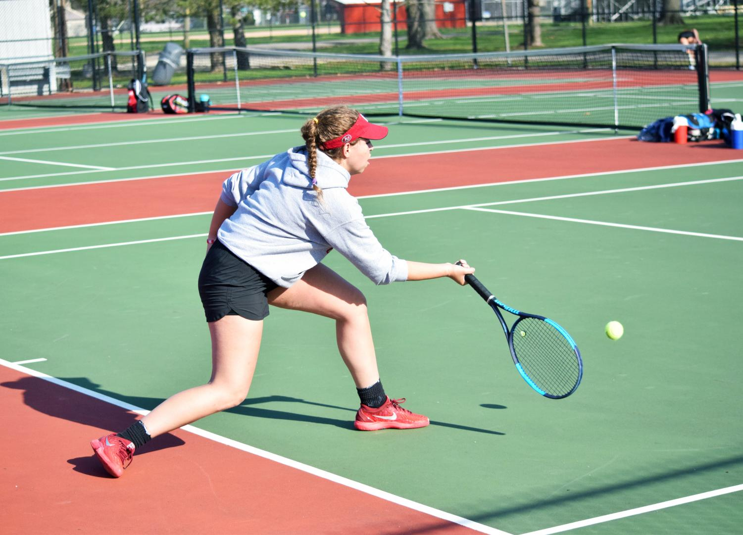 Junior Camille Khelseau returns the ball to her opponent in the first set of her match on April 17. Khelseau played first singles and lost in a very close tie breaker in the third set.