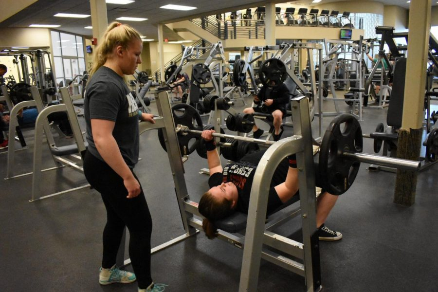 Junior Alexis Zrebiec (right) bench presses as her trainer, Chelsea Moore (left) spots her.