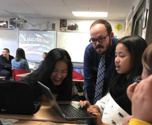 Spanish teacher Conner McNeely helps Mónica Par and Gracy Hmung during class.