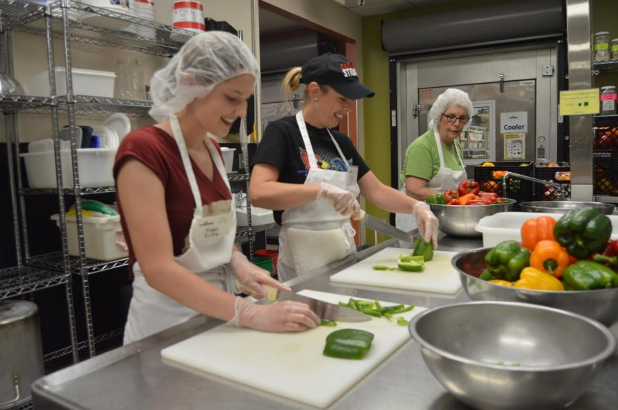 Senior Megan Irving cuts bell peppers with nutrition teacher Raye Jordan on Thursday, May 10. Irving and Jordan enjoy volunteering to help others.