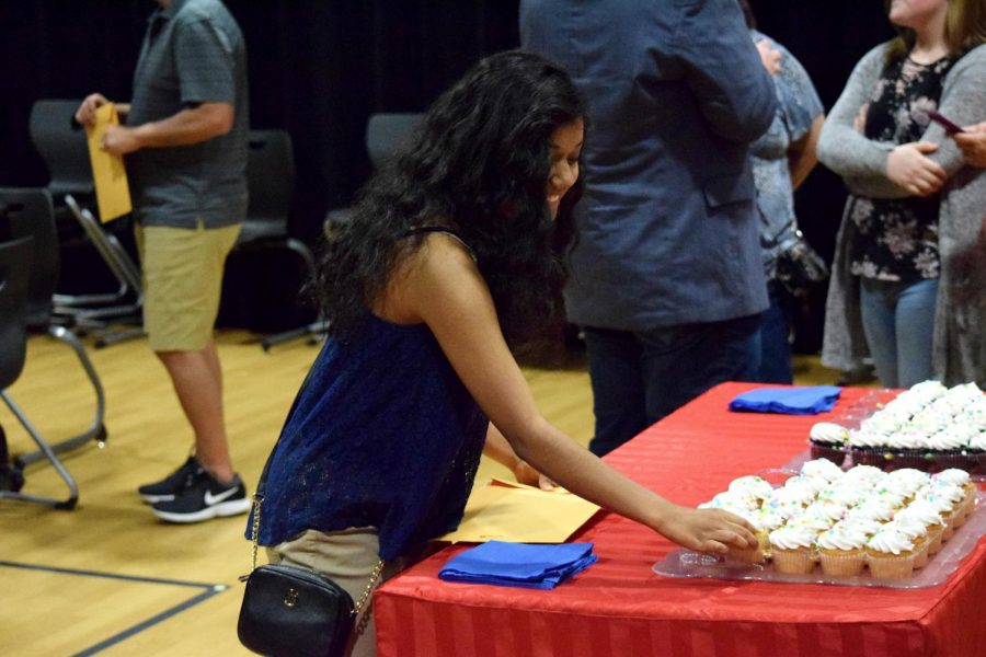 Junior Priscilla Garcia grabs a cupcake at the reception after the induction ceremony.