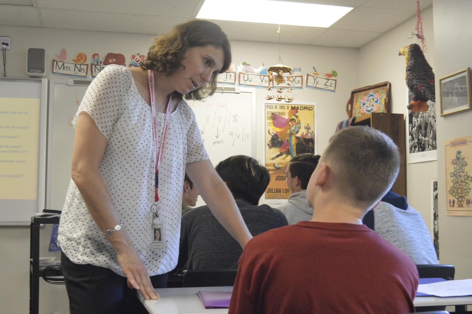 Foreign language teacher Jamie Marshall helps sophomore Blake Ward while wearing her photo identification.
