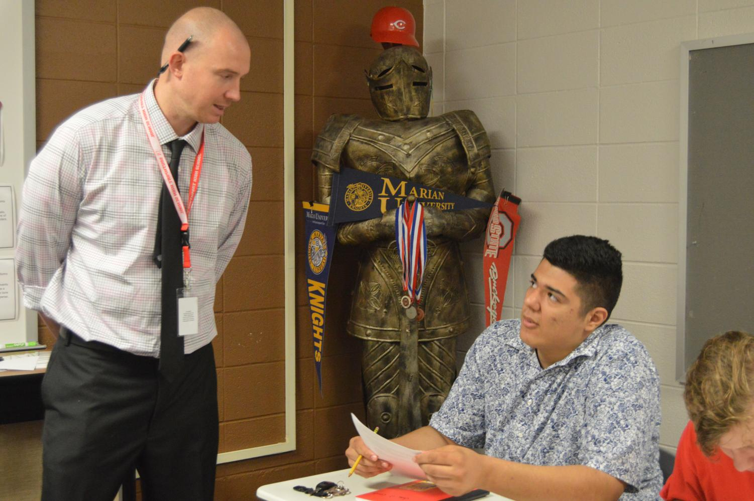 English teacher, Jordan Dever (left), works with senior Juan Cerda during class. This is Dever's first year teaching at SHS.