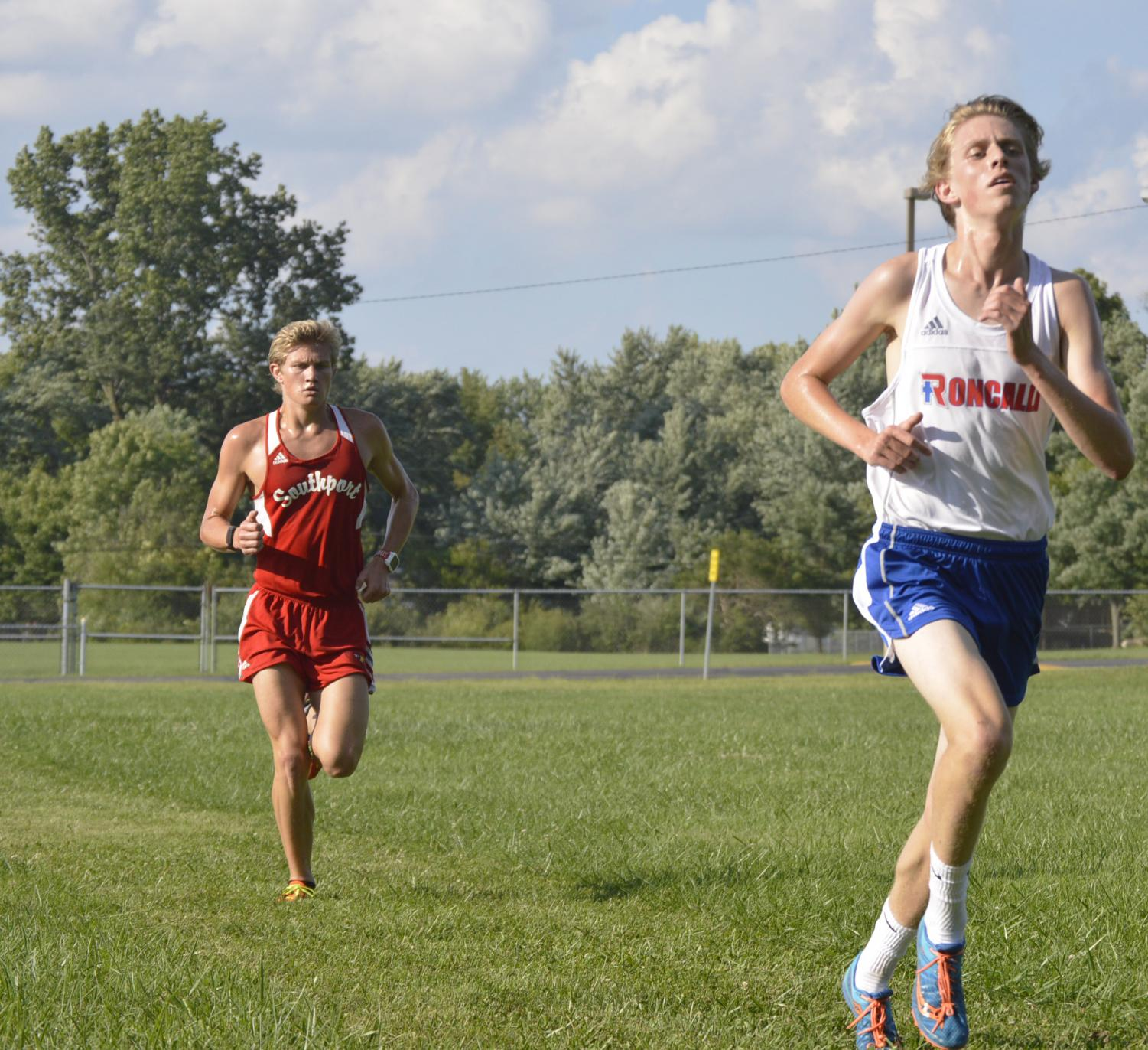 Junior++Drew+Shelinburger+runs+directly+behind+a+Roncalli+opponent.+Shellenbergerr+came+in+second+place+in+the+race.
