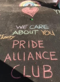 The pride alliance club drew pictures with sidewalk chalk to symbolize their club. They hope to spread messages to other students by doing this.