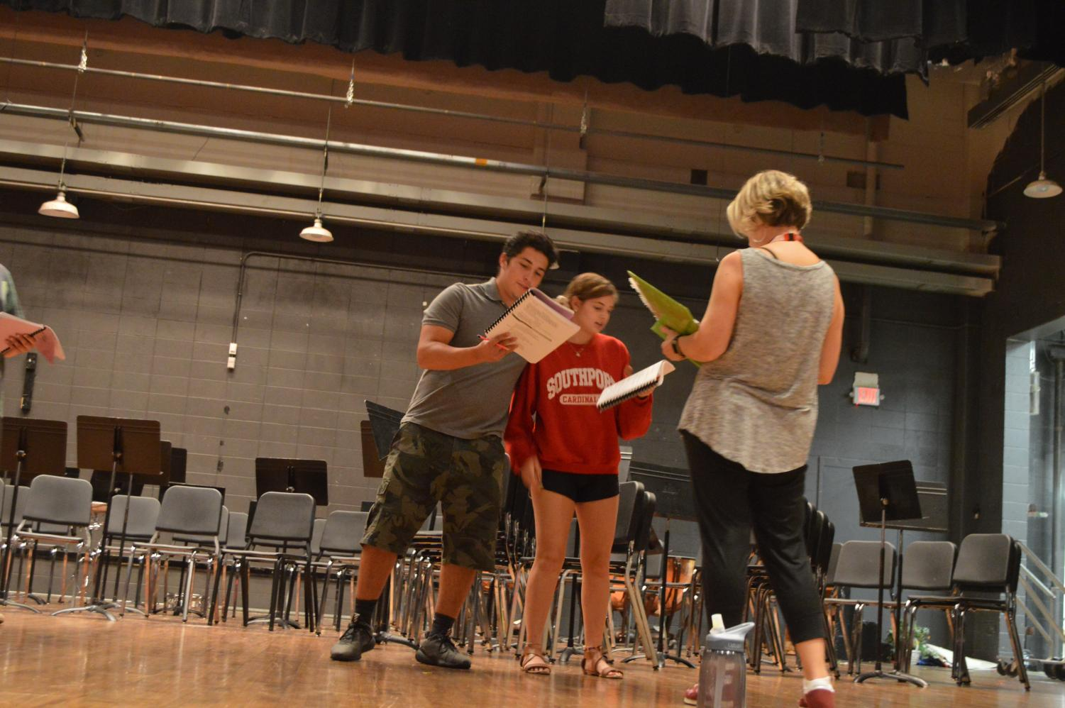 Theater teacher Kim Roberts oversees seniors Alyssa Smith and Sebastian Perez as they run through their lines.