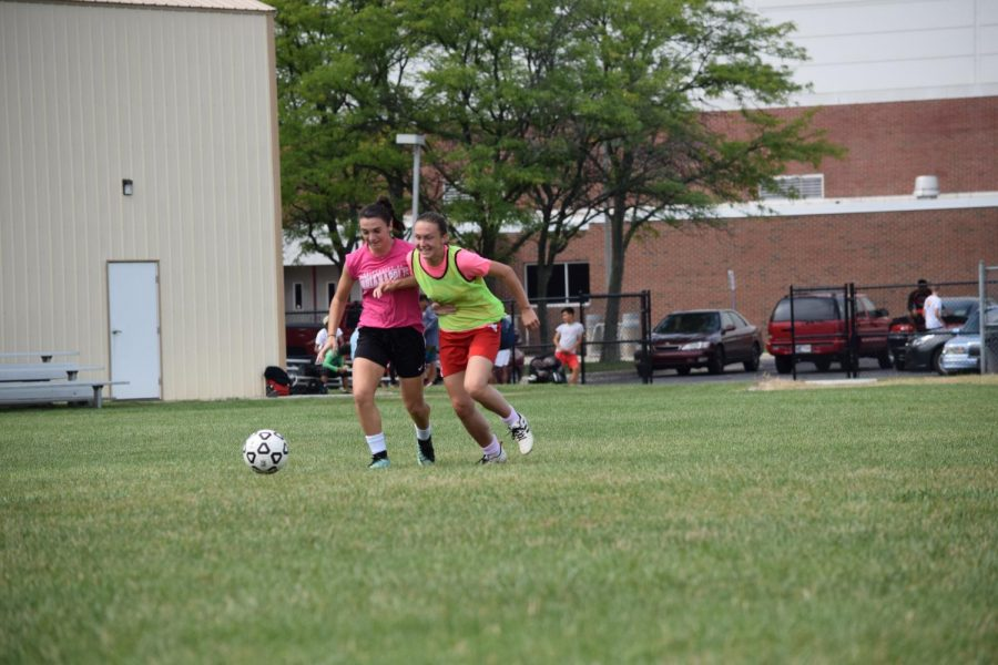 Sophomore Emma Main (left) and senior Jordan Cox (right) chase the ball at a practice on Aug. 9.