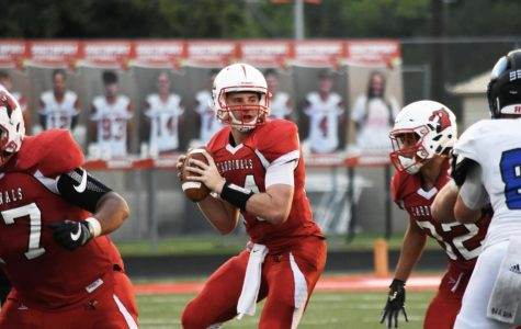 Senior quarterback Eddie Schott prepares to throw the ball to senior receiver Rashawn Haskins, ending in a touchdown for the Cardinals on Friday, Aug. 31.