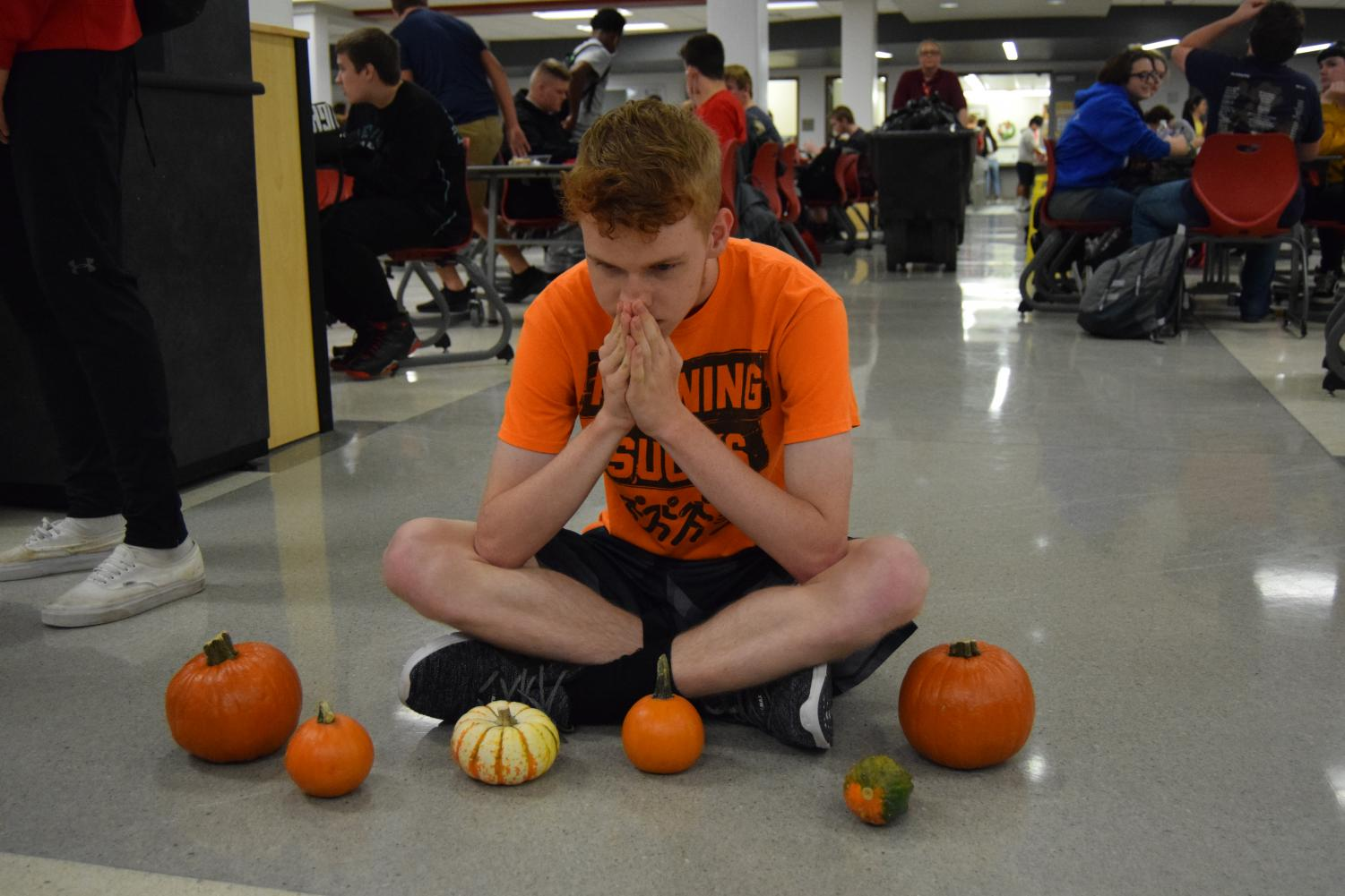 Junior Pam Grady sits as he is surrounded by pumpkins