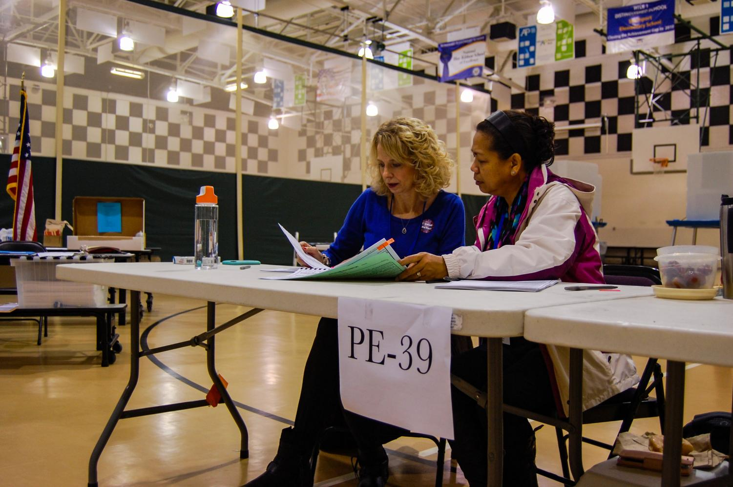 Poll workers from Precinct 39 go over paperwork and forms at the PTEC voting site on Nov. 6.
