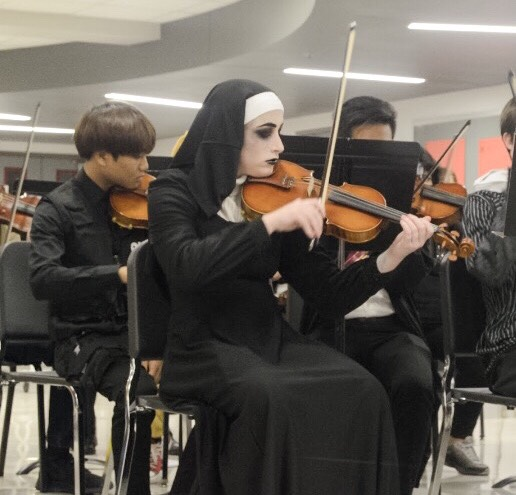 Senior Abby Dunn plays the violin in the SHS Halloween concert dressed as the antagonist in the recently released movie,