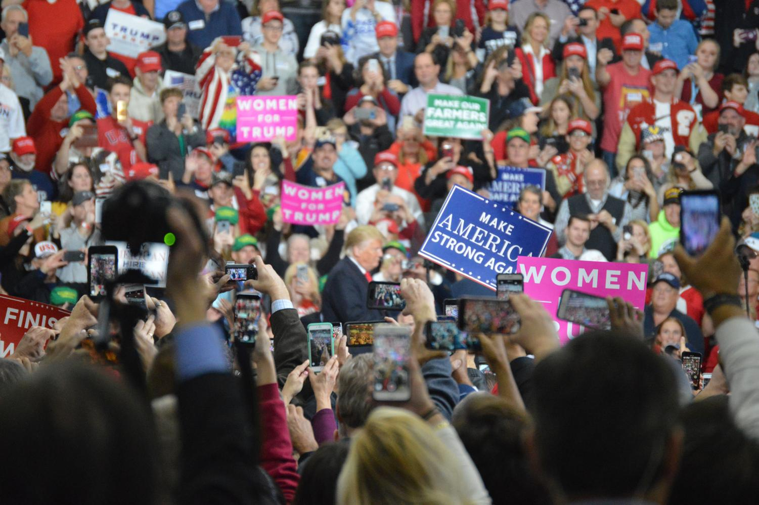 Rally attendees snap pictures, shoot videos and cheer as President Trump takes the stage.