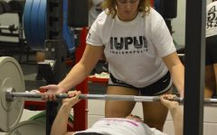 Senior Kenzie Lukas spots her lifting partner as they bench press on Nov. 6.