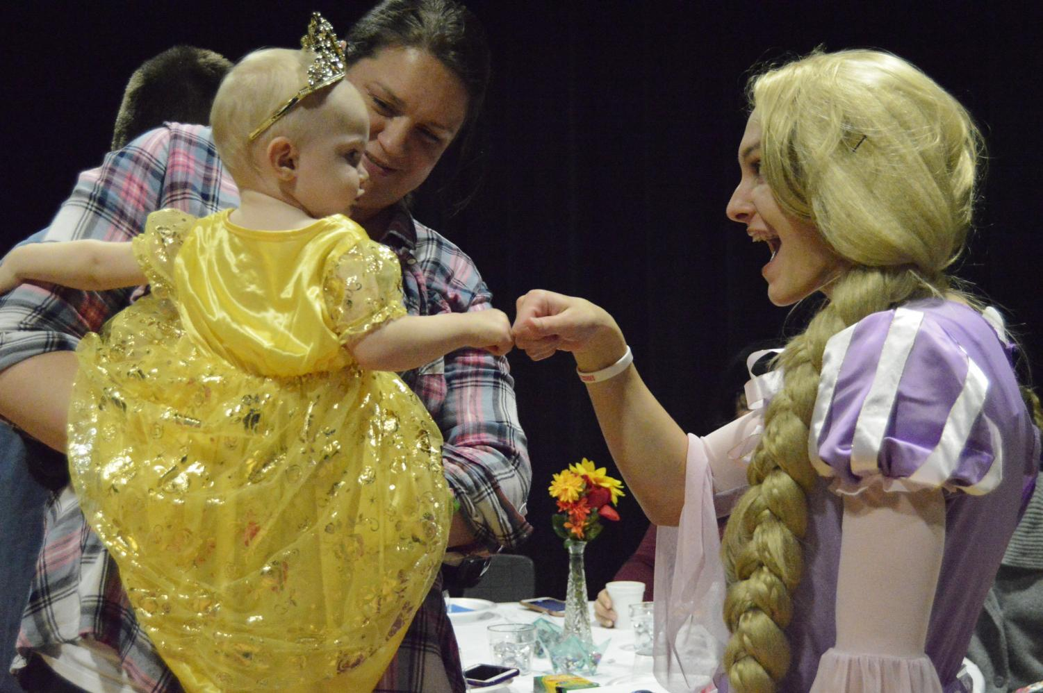 Senior Jordan Cox fist bumps with a child who attended Tea With A Princess. Cox was dressed and portraying the role of the Disney princess Rapunzel.