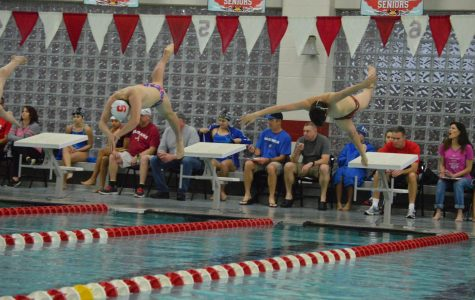 Senior Drew Reinke (left)dives into the pool to start the 200-yard freestyle. He finished in first place with a time of 1:48.17.