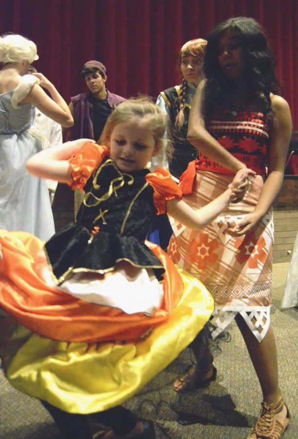 Senior Priscilla Garcia spins a child during the Tea with a Princess dance party dressed as the Disney princess, Moana.
