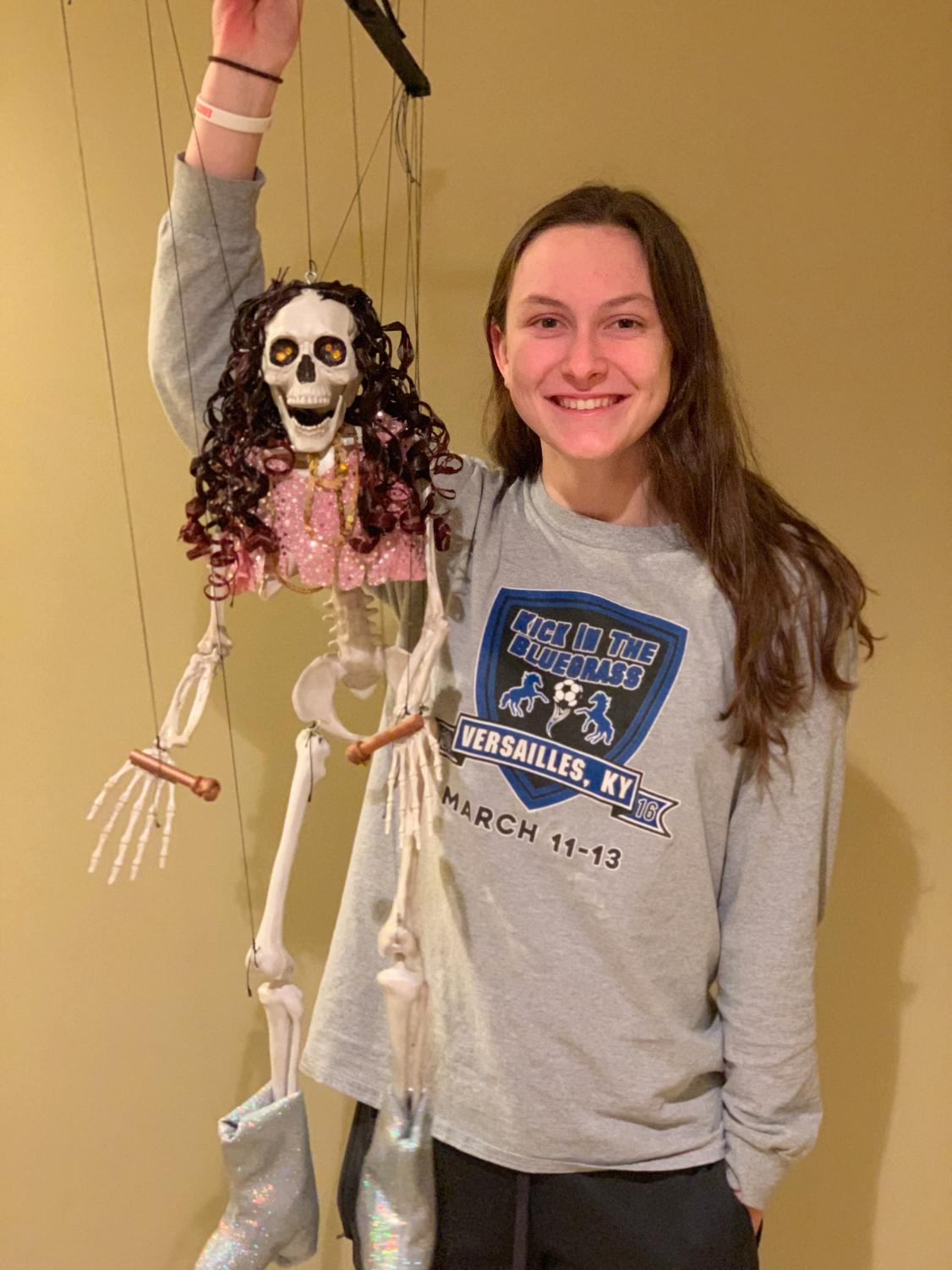 Senior Jordan Cox poses with one of the puppets that is used in performances at Peewinkle's Puppet Studio. Cox personally hand-made the puppet shown.
