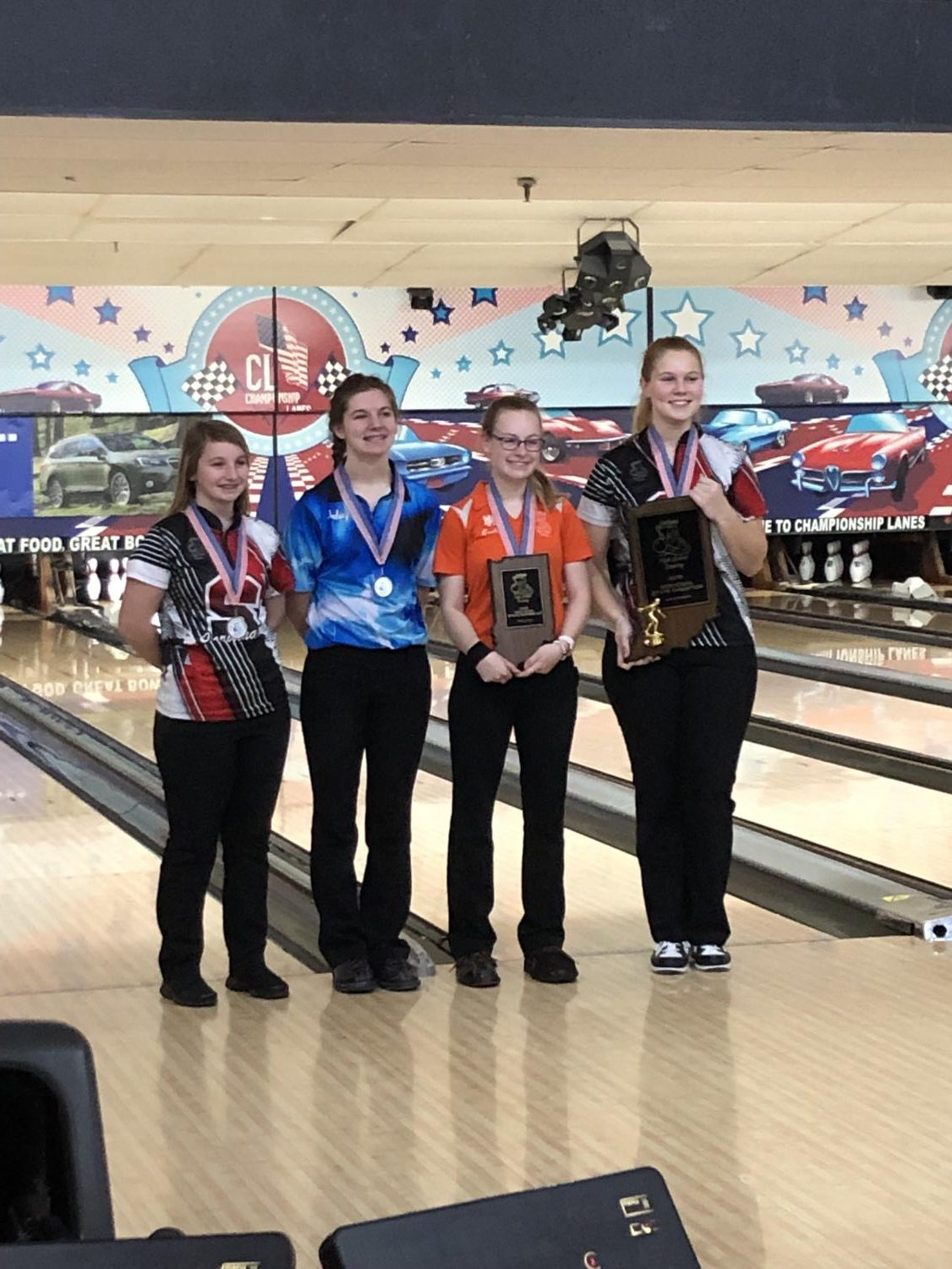 Senior Melissa Bushong (far right) receives her state championship bowling trophy on Feb. 2.