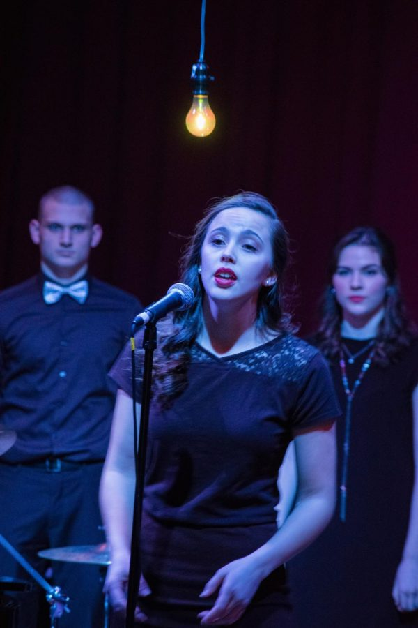 Senior Alyssa Hightower takes turns singing at the mic with other soloists during the April in Paris ensemble.