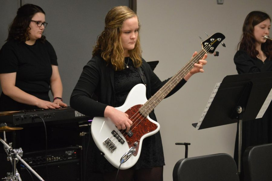 Senior+Abigail+Sullivan+plays+her+guitar+with+the+rest+of+the+band+during+warm+ups.+