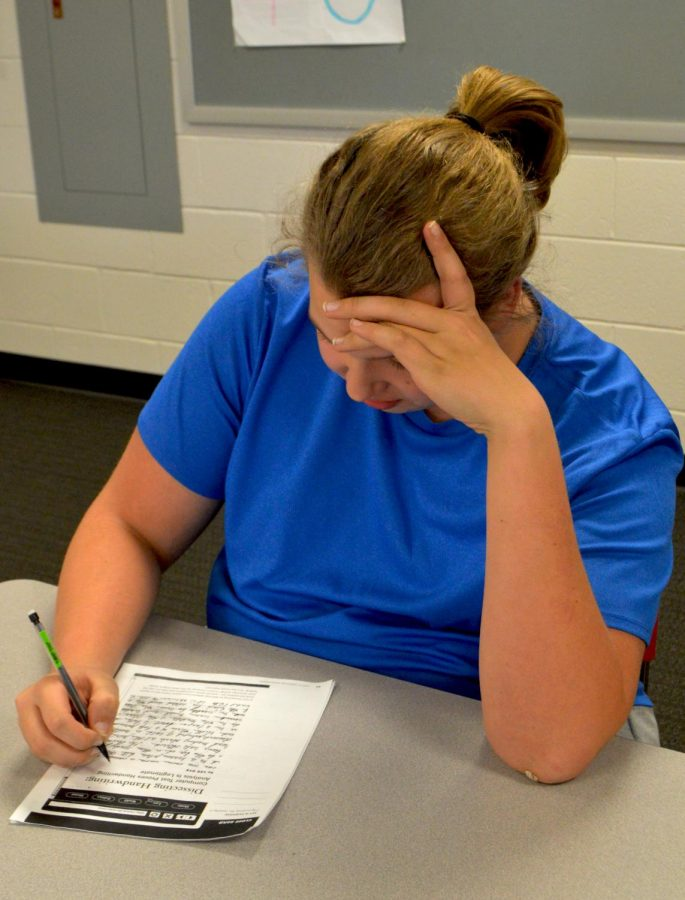 Junior Tom Stukkagan works on a pre-written exam provided by College Board as part of the student pilot program.
