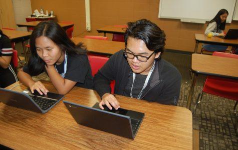 Estudiantes trabajan en companeros en la clase de idioma extranjero chino. Contactan con su maestra por la computadora