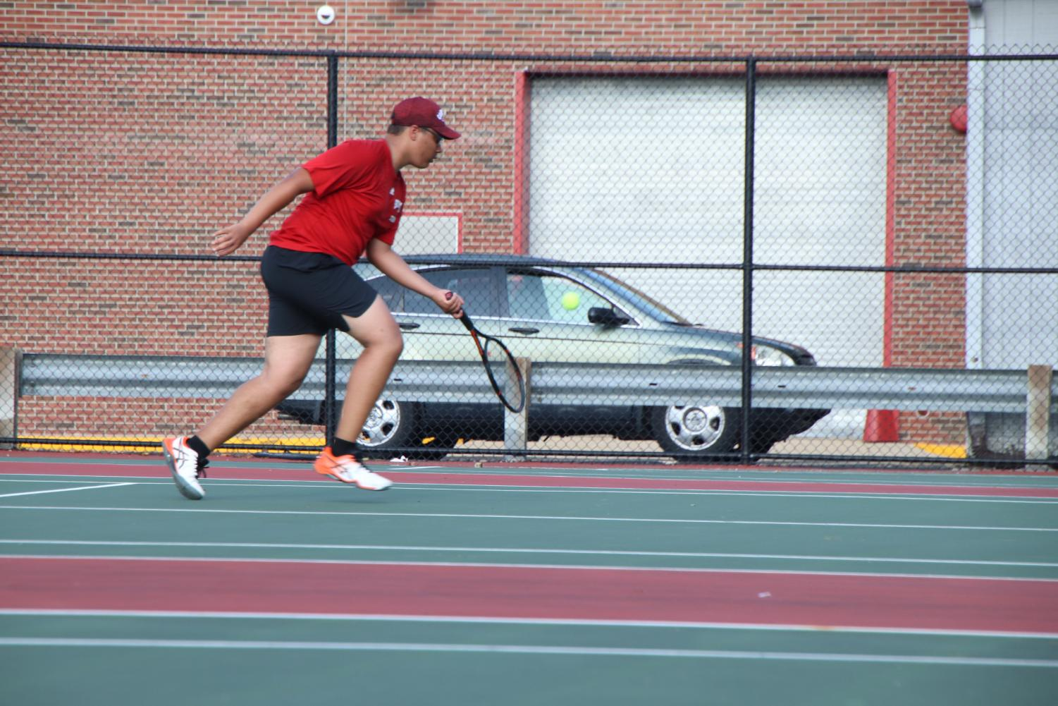 Senior+Brendan+Tyner+runs+up+to+hit+the+tennis+ball+during+his+singles+match.+Tyner+ended+up+losing+1-6+and+3-6.