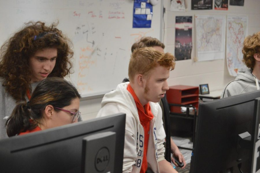Junior Ethan Henderson battles it out against a friend while sophomore Kaden Click watches over his shoulder on Nov. 12. Competitors like Henderson play on computers or other devices while waiting to use the Smartboard.