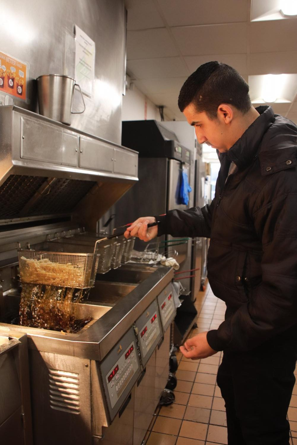 Saeed works on the fryer on Nov. 5. He started working at McDonald's only three months after fleeing Syria and is now a manager at his store.
