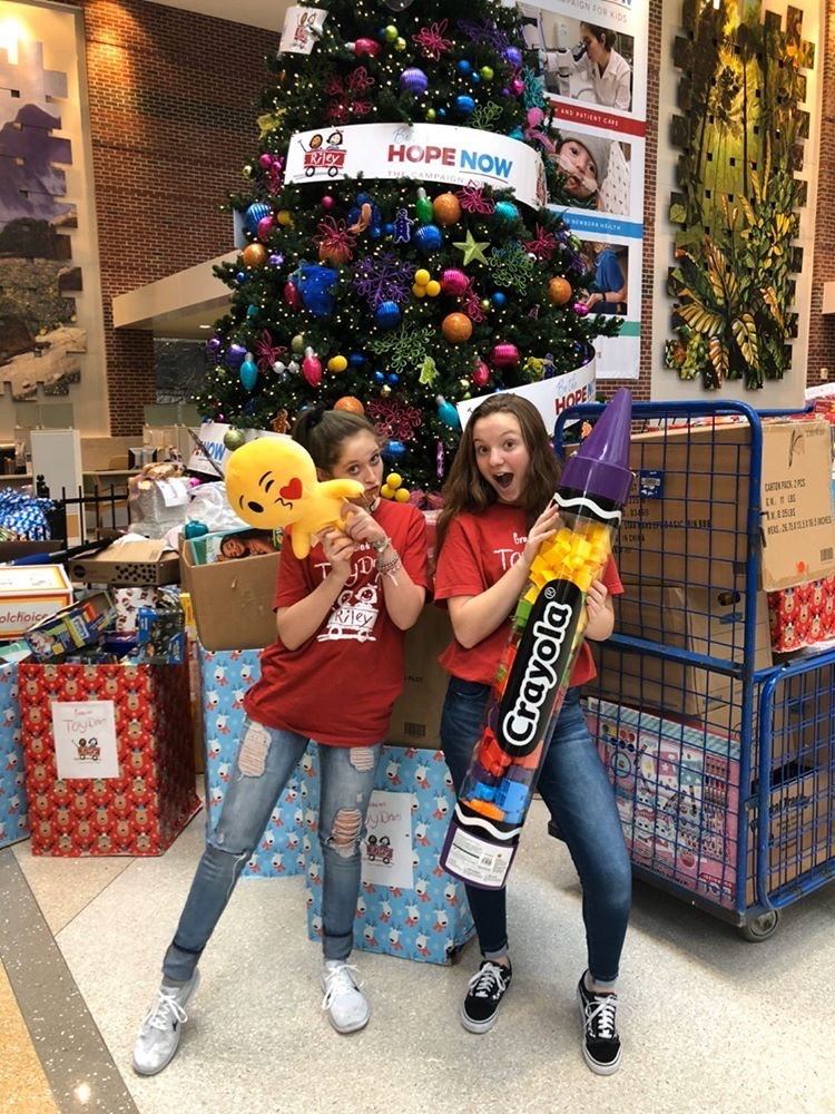 Gracie Bennett (left) and sophomore Ellie Brown pose with some of the donated toys at Riley Hospital. Gracie's goal is 15,000 toys.