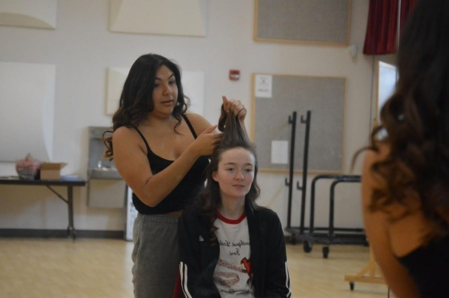 Junior Jennifer Sahagun does junior Grace Blume's hair. For a performance the girls have to have matching hair and stage makeup.