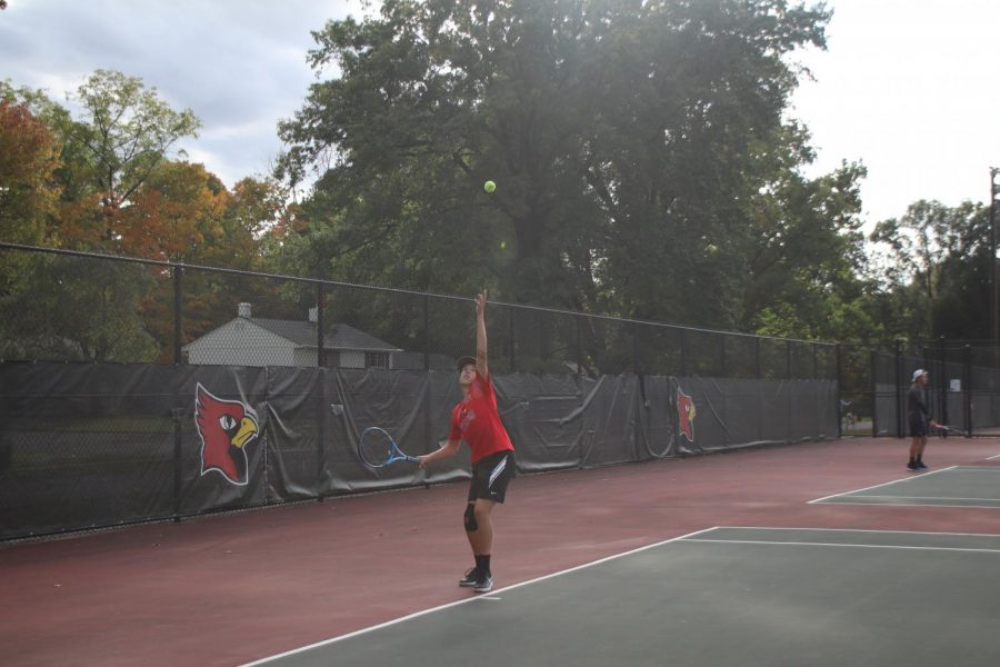Junior Micah Fishel tosses the ball up to serve. The Cards tennis team began their tennis sectional on Sept. 30.