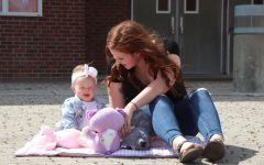 Senior Kayla Kinnamin plays with her daughter Skylar outside of SHS. Kinnamin became a mother six months ago and says she is trying her best to tend to her responsibilities.