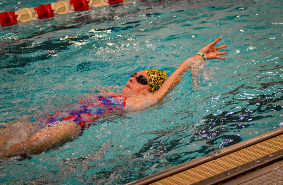 Freshman Dorrie June swims backstroke during warm ups.