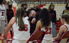 Girls basketball head coach Adam Morelock draws up a play during a timeout. The Lady Cards will only be allowed two spectators per player because of new guidelines.